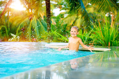 Cute happy little boy in the pool, active kid playing in the poolside, enjoying summer holidays on the exotic beach resort photo