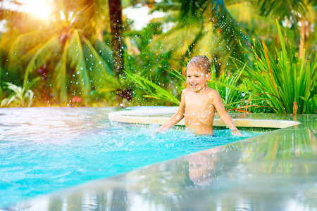 Cheerful boy standing in the pool and with pleasure splashing cold refreshing water, happy child playing in the swimming pool, active summer holidays, having fun on the beach resort in exotic country photo