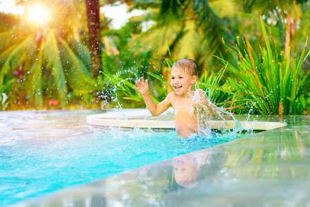 Cheerful boy standing in the pool and with pleasure splashing cold refreshing water, happy child playing in the swimming pool, active summer holidays, having fun on the beach resort photo