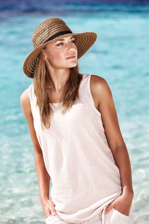 Portrait of a pretty woman on the beach over blue water background, dreamy mood, fashion look for summer vacation