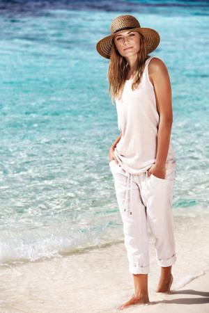 魅力的なモデルが着ているベージュの素敵な服と帽子、水を歩いてビーチに美しい女性は、海のそばの夏休みを楽しんでいます。 写真素材