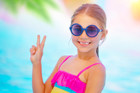 Portrait of a pretty baby girl wearing cute sunglasses on the beach, sweet kid smiling and shows the sign of peace by hand, happy summer vacation in the pool photo