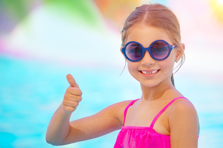 Portrait of a cute little smiling girl on the beach gesturing good mood, thumbs up, having fun near the sea in the swimming pool, happy summer vacation photo