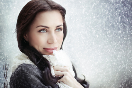 Portrait of a beautiful dreamy woman standing under the rain on a cold autumn day, gorgeous fashion look, natural beauty