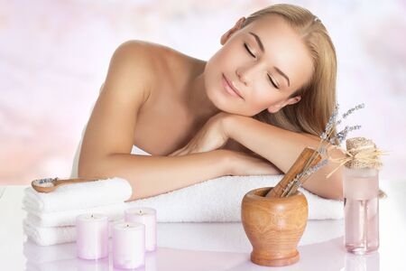 Portrait of a beautiful calm woman sleeping on massage table, closing eyes of pleasure, enjoying medical and beauty procedure, day spa concept Stock Photo