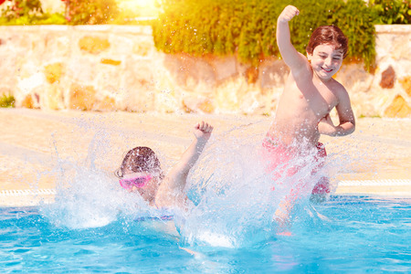 Two happy children in the pool, little girl and boy jumping into the cold refreshing water, active summer vacation, enjoying holidays on the beach resort