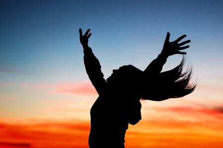 다채로운 하늘 배경 위로 제기 손으로 쾌활 한 여성의 일몰, 실루엣을 즐기는 행복 한 여자, 자연의 아름다움 존경