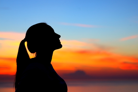Profile silhouette of a beautiful woman standing outdoors and enjoying silence on colorful sunset sky background Stock Photo