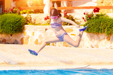 Joyful girl jumping to the pool, cute little child wearing goggles and flippers for diving, happy carefree childhood, enjoying summer holidays on the beach resort Reklamní fotografie - 81707176