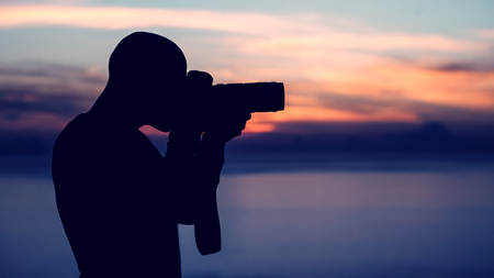 Photographer taking pictures outdoors, silhouette of a man with camera over sunset background, photographing beautiful view of wild nature photo