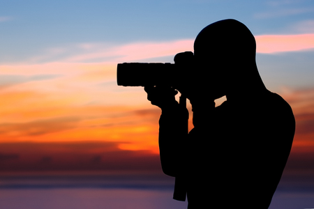 Photographer taking pictures, silhouette of a man with camera over beautiful orange sunset background, photographing amazing view of a nature near the beach photo