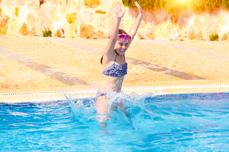 Happy little girl jumping to the pool, active child swimming in poolside with a splash of water, summer travel and tourism photo