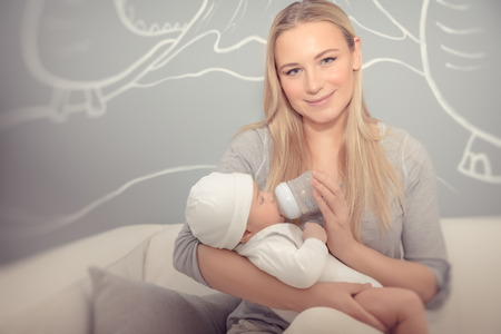 Happy mother feeding her adorable newborn baby, nice young mom with pleasure spending time at home with her child, enjoying parenting