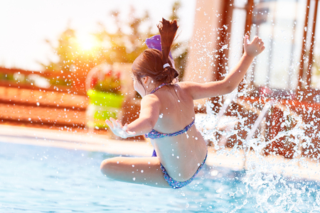 Active joyful little girl jumping to the water, having fun in the swimming pool on the beach resort, happy holidays in the summer camp photo