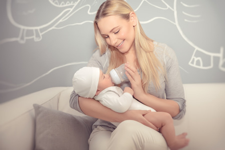 Cute mother feeding her adorable newborn baby in the beautiful cozy kids room at home, special milk formula for infants, enjoying parenthood, happy family life