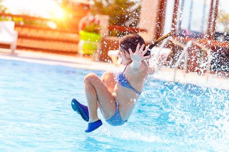 Niña alegre activa saltando al agua, divirtiéndose en la piscina en el resort de playa, felices vacaciones de verano Foto de archivo - 81914407