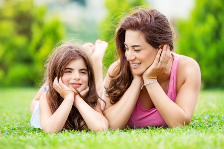 Portrait of a mother with little pretty daughter having fun together outdoors, lying down on the meadow, relaxing in a countryside, happy family life photo