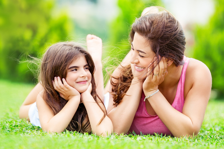 Portrait of a mother with little pretty daughter having fun together outdoors, lying down on the meadow and looking on each other, spending summer holidays in a countryside, happy family life photo