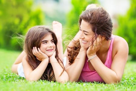Portret van een moeder met een mooie, mooie dochter die buitenshuis plezier heeft, op de weide ligt en op elkaar kijkt, zomervakantie in een platteland, een gelukkig gezinsleven doorbrengen