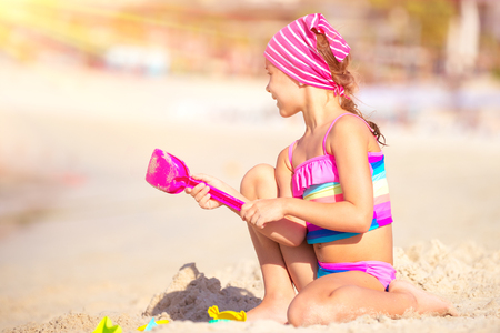 Happy little girl playing on the beach with plastic toys, active childhood, having fun outdoors, enjoying summer holidays on the seashore Stock Photo