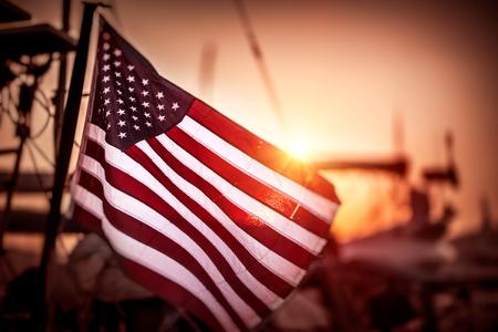 アメリカ合衆国の旗がはためき穏やかな夕日の光、アメリカの独立記念日の風で
