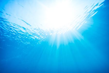 Prachtig uitzicht vanaf onderwater, zonnestralen door het oppervlak van het water, onderwater duiken, blauwe water achtergrond Stockfoto