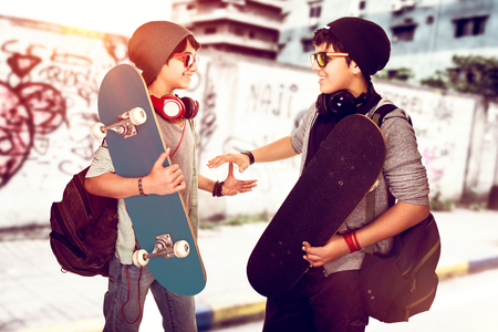 Joyful boys greeting each other on the street, happy active skateboarders having fun together, urban lifestyle, stylish modern life of youth Banco de Imagens