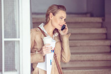 Portrait of a beautiful blond student girl talking on the phone and drinking coffee, using smart technology for work and communication, modern life of young people photo