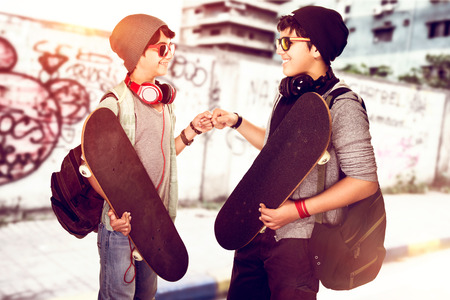 Happy young skateboarders greeting each other on the street, best friends with active hobby, enjoying outdoors sport, cool urban life