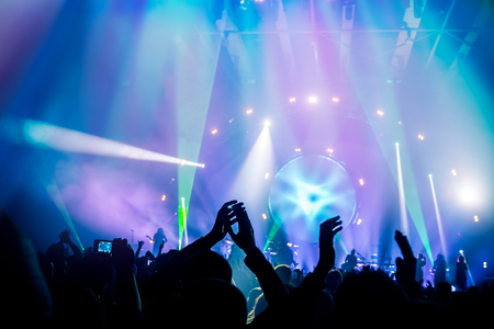 Many people enjoying concert, band performs on stage in the bright blue light, people enjoying music, dancing with raised up hands and clapping, active night life Foto de archivo