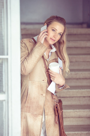 Serious business woman talking on the phone, female at work, discussing business, using modern technology of communication photo