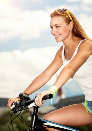 Beautiful happy woman riding the bicycle in countryside, pretty female enjoying time spending on open air, healthy lifestyle, active summer vacation photo