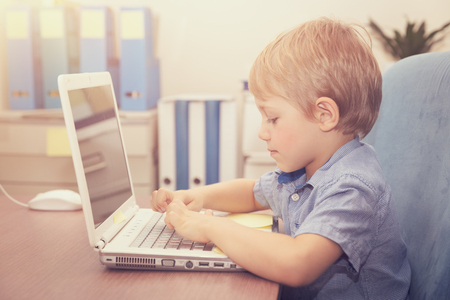 Little boy working on the laptop at home, cute schoolboy doing homework using wireless internet, typing on the computer, back to school concept photo
