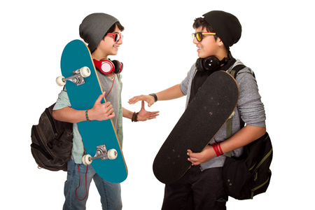 skateboarder: Two happy skateboarders acclaiming each other isolated on white background, best friends wearing stylish hats, sunglasses and listening music from earphone, modern life of a young people