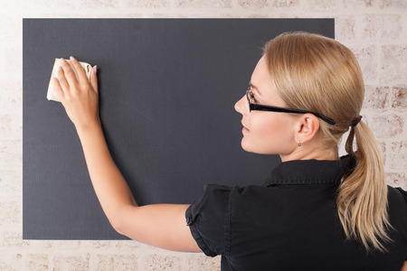 Student girl cleaning blackboard in the classroom, text space on the chalkboard, education in the university, getting knowledge in the high school Stock Photo