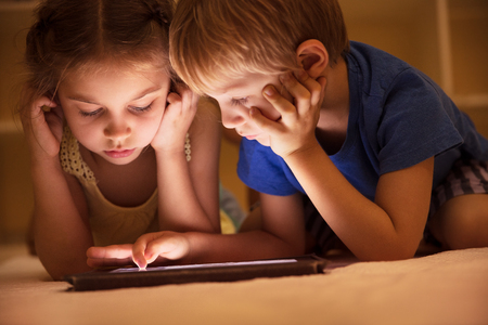 Portrait of a two cute little kids lying down on the floor and watching animated cartoons on the tablet, brother and sister with pleasure spending time together at home   Stock Photo