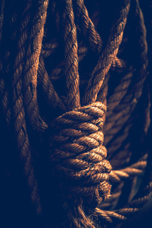 Dark closeup photo of a rope knot, abstract background, safety equipment on the ship, old vintage picture