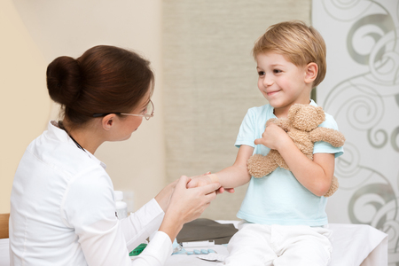 Cute smiling boy at the doctor with his little toy friend, not affraid to visit pediatrician, happy healthy childhood