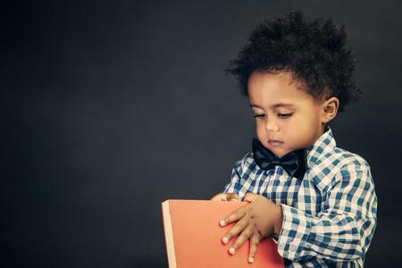 Portret van een schattige kleine schooljongen met boek in handen over schoolbord achtergrond, basisschool, terug naar school concept