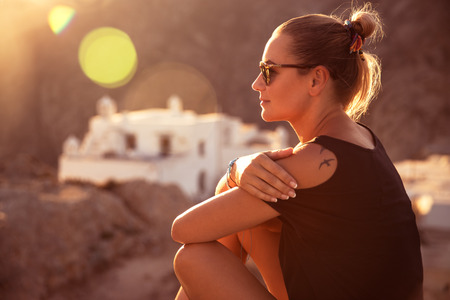 Beautiful traveler girl sitting on top of the mountain and enjoying amazing view on the monastery in sunset light, visiting beautiful places, peaceful spiritual summer vacation