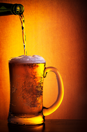 Tasty cold beer poured from the bottle to the glass over orange background, refreshing alcoholic drink, Oktoberfest celebration Stock Photo