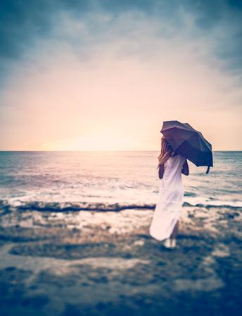 슬픔 개념, 우산 해변에서 여자의 후면보기 폭풍우 치는 바다, 외로운에 찾고 흐린 날씨에 소녀
