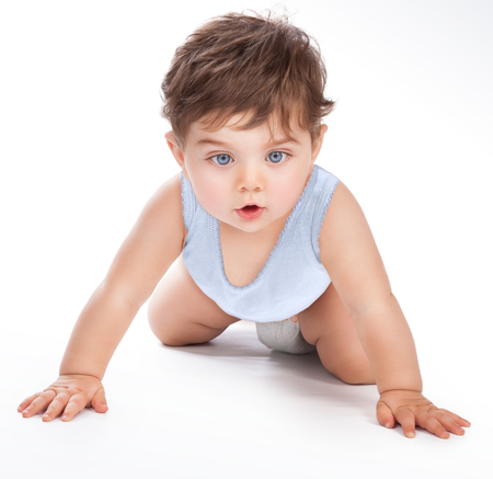 Portrait of a cute sweet baby crawling in the studio, pretty boy isolated on grey white background, little child want to discover everything