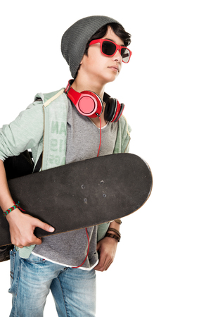 Skateboarder over white background, cute teen boy wearing stylish hat and glasses listening music, wearing headphones, sportive hobby of a young guy Stock Photo