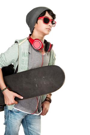 Skateboarder over witte achtergrond, leuke tienerjongen die modieuze hoed en glazen het luisteren muziek draagt, die hoofdtelefoons, sportieve hobby van een jonge kerel draagt Stockfoto