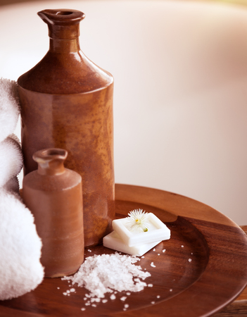 resort life: Beautiful bathroom still life, two brown ceramic bottles on the wooden plate with sea salt and soap, spa and body care concept