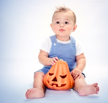 Cute little baby boy sitting in the studio over clear background with carved orange pumpkin, happy Halloween day, traditional American autumn holiday