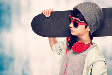 Portrait of a stylish teen boy wearing sunglasses and hat holding in hand skateboard over grunge background, modern life of youth 免版税图像