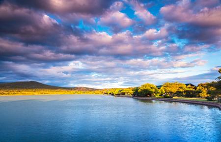 晴れた日、湖とそれ、パノラマ ビュー、南アフリカ共和国の素晴らしい自然にふわふわ雲がかかる山の美しい風景のガーデン ルート