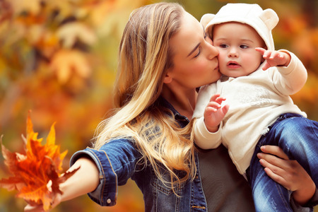Portrait of a happy mother holding her precious little son, kissing him and showing to him dry maple leaves, having fun in the autumn park